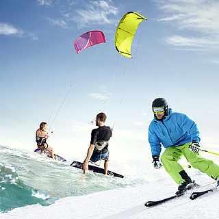Im Vordergund sind zwei Personen am Snowboarden imSchnee. im Hintergrund sind zwei Personen, die auf dem Wasser wakeboarden
