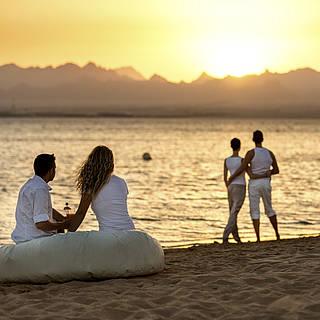 Paare schauen sich den Sonnenuntergang am Meer an