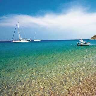 Kieseliger Strand mit klarem Wasser und zwei weißen Booten, im Hintergrund Berge