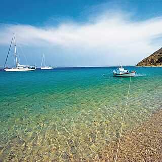 Kieseliger Strand mit kristallklarem Wasser auf dem drei Boote sind
