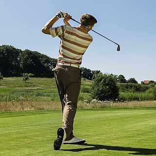 Mann auf dem Golfsplatz, nach dem Abschlag