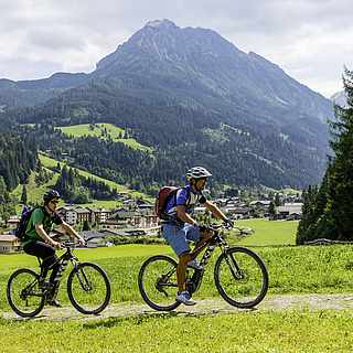 3 Radfahrer die durch ein Tal fahren