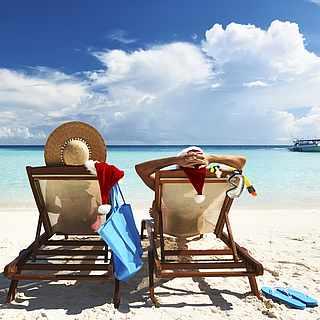Zwei Personen auf Sonnenliegen blicken aufs weite Meer