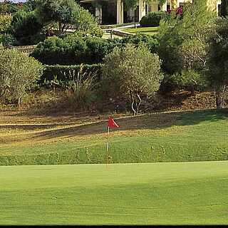 Blick von hügelig-gepflegter Golflandschaft auf Villa