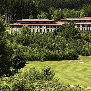 Grüne Wiese, auf der ein Ball liegt; im Hintegrund ein Golfplatz