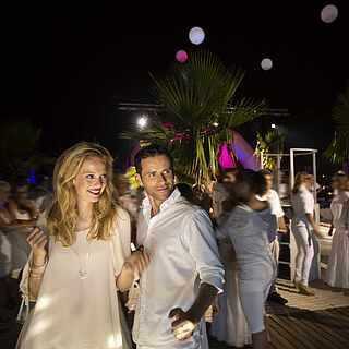 Mann und Frau im weißen Outfit auf der Tanzfläche
