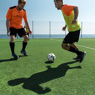 Zwei Männer spielen Fußball in der Sonne und mit Schattenfiguren