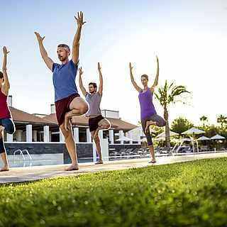 Vier Personen machen Yoga und Pilates draußen am Pool