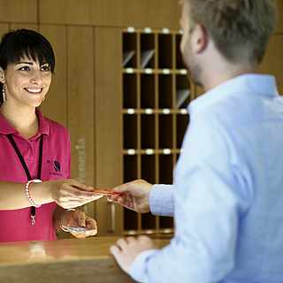 Rezeptionistin übergibt einem Kunden seine Zimmerkarte