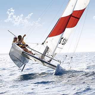 Ein weißer Katamaran mit weiß-rotem Segel. Ein Mann und eine Frau tragen schwarz-orangene Schwimmwesten und sitzen auf der linken Seite des Katamarans. Der Katamaran befindet sich in deutlicher Schieflage, sodass sich der linke Rumpf in der Luft befindet. Der Himmel ist blau mit kleinen Schleierwolken und der Katamaran ist von Wasser umgeben.