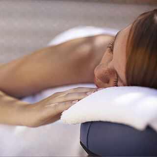 Eine Frau liegt auf einer Massageliege und hat die Augen geschlossen. Sie ist zugedeckt mit weißen Handtüchern.