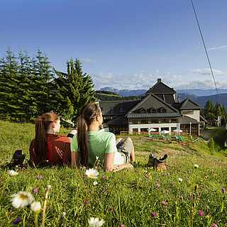 Zwei Wanderinnen liegen auf Bergwiese und schauen auf Berge und Hütte