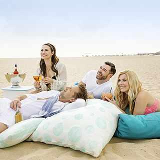 Zwei Pärchen sitzen zusammen am Strand auf Sitzkissen und trinken leckere Drinks