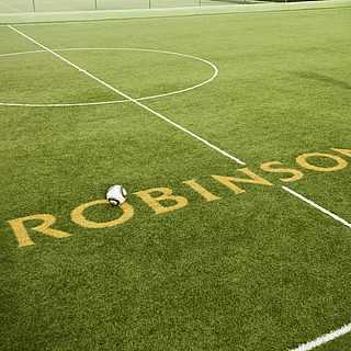Ein Mann schießt einen Fußball über den Schriftzug von ROBINSON