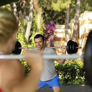 Eine Frau und ein Mann heben schwere Gewichte.