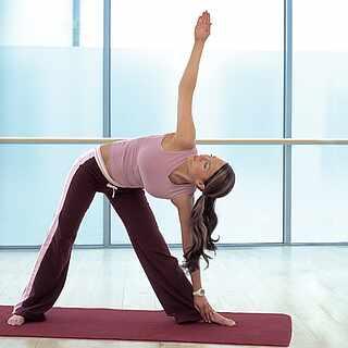 Eine Frau macht auf einer Yogamatte eine Position. Sie trägt Sportkleidung und ist in einem Raum.