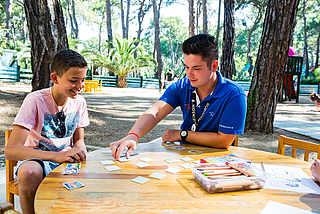 Kind sitzt mit einem Betreuer an einem Tisch und spielt Karten