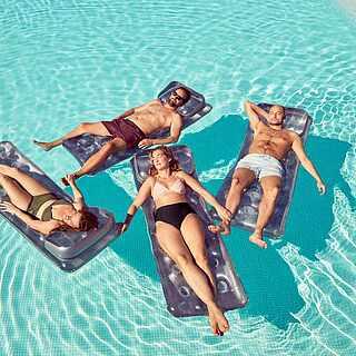 Vier Personen auf Luftmatratzen im Pool
