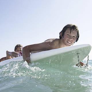Junge liegt auf einem Surfbrett im Wasser