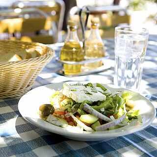 Gedeckter Tisch mit Vorspeisensalat, Olivenöl und Brotkorb auf weißblau-karierter Tischdecke