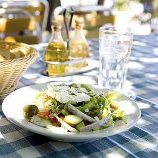 Gedeckter Tisch mit Vorspeisensalat, Brotkorb und Olivenöl auf weiß-blau-karierter Tischdecke