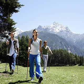 Eine Gruppe von Menschen läuft durch eine Gebirgslandschaft.