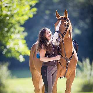 Reiterin mit Pferd im Wald