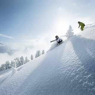 Zwei Skifahrer, die eine Piste runterfahren