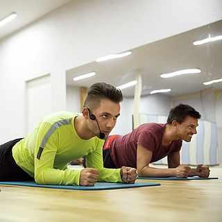 Drei Personen machen die Plank-Übung. Sie sind in einem Spiegelraum.