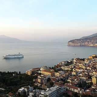 Blick von Oben auf eine Stadt am Meer, großes Schiff im Wasser