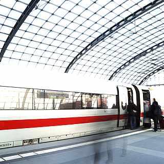 Im Bahnhof steht ein zug der DB, in den Leute einsteigen