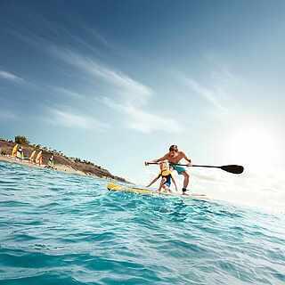 Ein Vater steht mit seinem Sohn gemeinsam auf einem Stand-Up-Paddle-Board