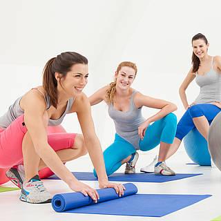 Frauen in Sportkleidung beim Pilates auf Sportmatten und mit Gymnastikbällen.