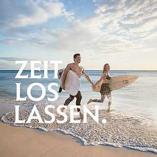 Ein Paar läuft mit Body Boards Hand in Hand am Strand entlang