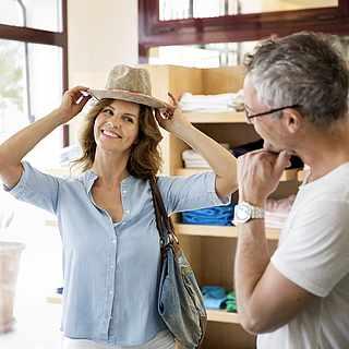 Frau probiert einen Sommerhut auf vor ihrem Mann im Geschäft