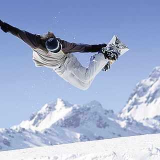 Snowboarder springt mit seinem Board in den Bergen in die Luft