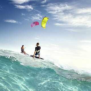 Zwei Menschen kiten auf türkis-blauem Meer