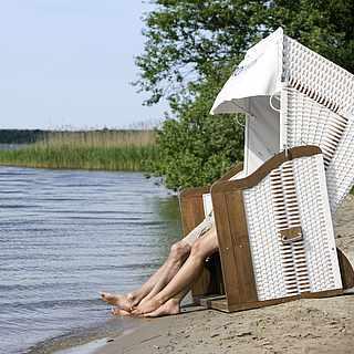 Strandkorb am Ufer des Fleesensees mit zwei Personen darin