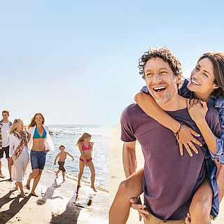 Familie und Paar am Strand