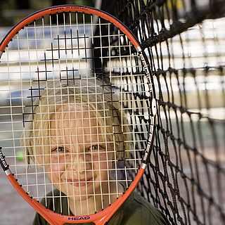 Ein Junge lächelt und hält sich einen Tennisschläger vor das Gesicht