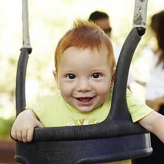 Lächelndes Baby in einer Babyschaukel
