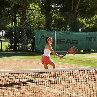 Frau spielt Tennis auf dem Outdoor-Tennisplatz