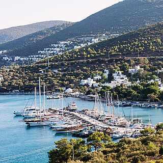Hügelige, grüne Küste mit Hafen und klarem Wasser