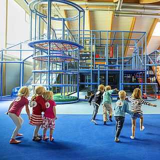 Kindergruppe und Betreuerin vor einem blauen Kletterlandschaft Indoor