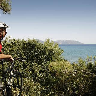 Ein Fahrradfahrer steht, auf sein Bike gelehnt, an einer Klippe. Man sieht im Hintergrund das Meer und Gebirge. Hinter dem Mann sieht man Bäume und Büsche.
