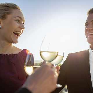 Ein Mann und eine Frau stoßen mit einem Glas Sekt ein