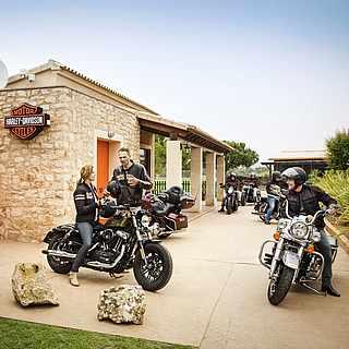 Sechs Motorradfahrer sind an ihren Motorrädern in Motorradkleidung. Im Hintergrund sieht man ein MOTOR HARLEY-DAVIDSON CYCLES-Gebäude
