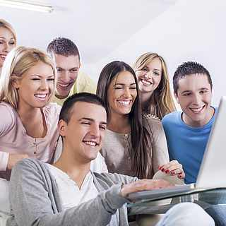 Eine Gruppe von jungen Leuten sitzt vor dem Laptop und will ihren ROBINSON Urlaub buchen