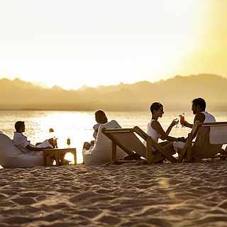 Gäste mit Getränken beim Sonnenuntergang am Strand