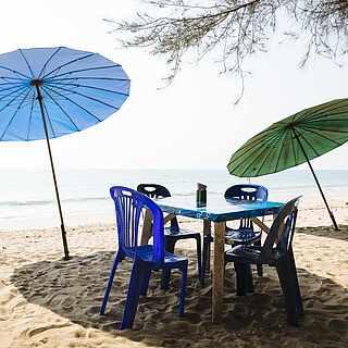 Ein Tisch am Sandstrand mit Ausblick auf das Meer